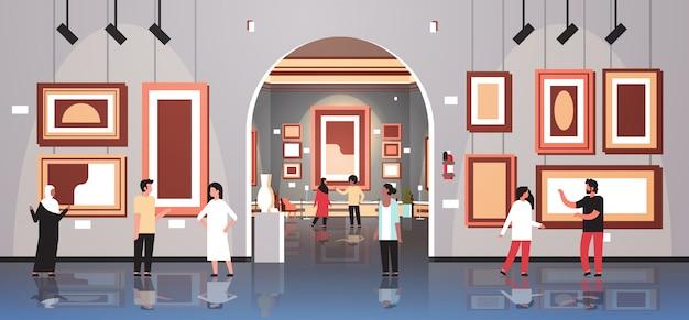 Gli spettatori dei turisti della gente nell'interno del museo della galleria di arte moderna che sembrano le opere d'arte contemporanea creativa delle pitture o le mostre orizzontali piane Vettore Premium