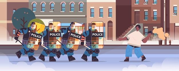 Poliziotti in completo equipaggiamento tattico agenti di polizia antisommossa che attaccano il manifestante con fumogeni durante gli scontri dimostrazione protesta Vettore Premium