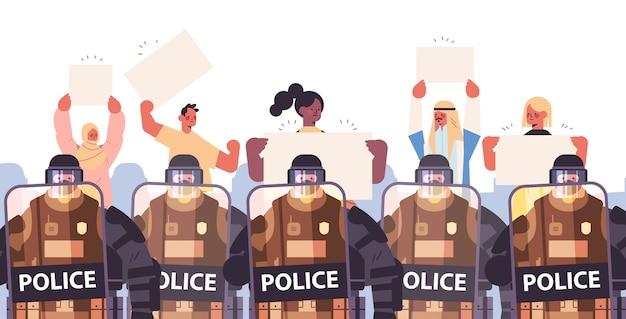 Poliziotti in completo equipaggiamento tattico agenti di polizia antisommossa che controllano i manifestanti di strada con cartelli durante gli scontri dimostrazione concetto di protesta Vettore Premium