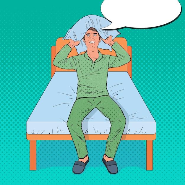Pop art angry man chiudendo le orecchie con il cuscino. situazione mattutina stressante. ragazzo che soffre di insonnia. Vettore Premium