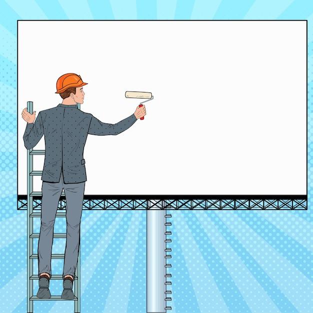 Uomo d'affari di pop art in casco con tabellone per le affissioni in bianco. lavoratore di sesso maschile che applica banner. concetto di pubblicità. Vettore Premium