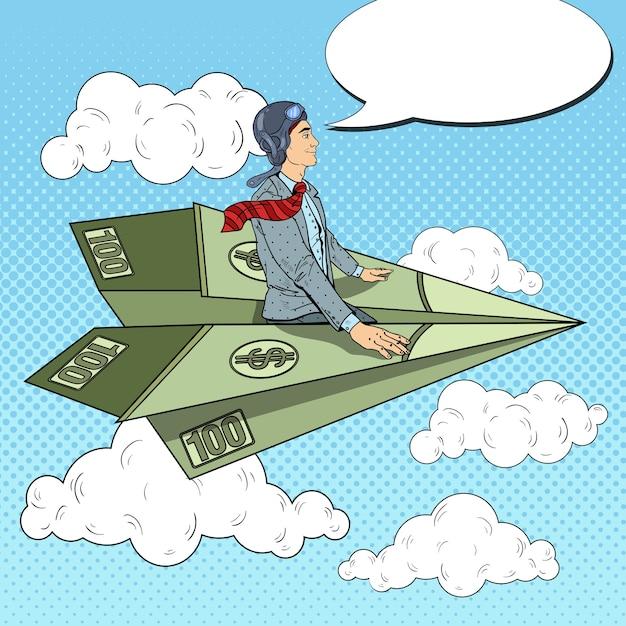 Uomo d'affari di successo di pop art volando sull'aereo di carta del dollaro. Vettore Premium