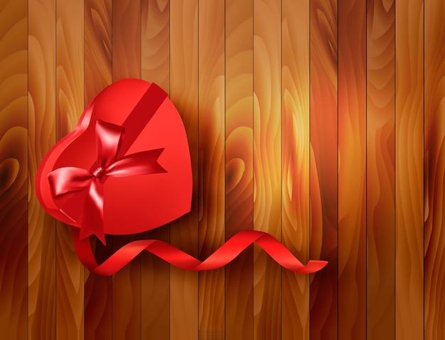 Confezione regalo rossa a forma di cuore con nastro su fondo in legno. Vettore Premium
