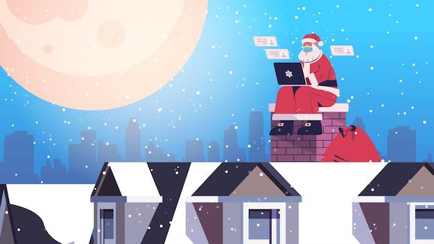 Babbo natale in maschera seduto sul tetto utilizzando laptop felice anno nuovo buon natale vacanze celebrazione concetto figura intera orizzontale illustrazione vettoriale Vettore Premium