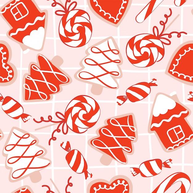 Modello senza cuciture con biscotti disegnati a mano di natale con glassa di zucchero nei colori rosso, rosa e bianco a forma di casa, albero di natale, ornamento, calzini, caramelle e tazza con cacao Vettore Premium