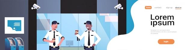 Uomini della guardia giurata che bevono caffè che lavora alla porta di entrata Vettore Premium