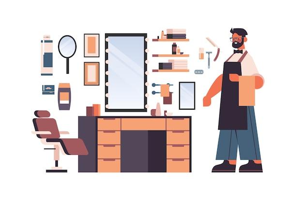 Impostare strumenti e accessori da barbiere con carattere di barbiere maschio nella raccolta uniforme di attrezzature da barba e parrucchiere isolato illustrazione vettoriale orizzontale Vettore Premium