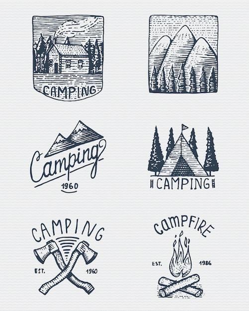 Set di incisi vintage, disegnati a mano, vecchi, etichette o badge per campeggio, trekking, caccia con picchi di montagna, casa, ascia e tenda, falò con foresta Vettore Premium