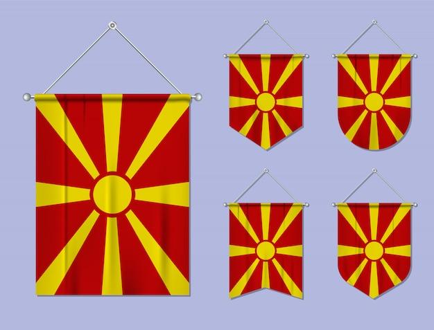 Set di appendere bandiere macedonia con trama tessile. forme di diversità del paese di bandiera nazionale. stendardo modello verticale Vettore Premium