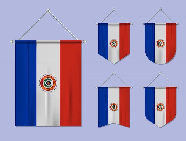 Set di bandiere sospese paraguay con trama tessile. forme di diversità del paese di bandiera nazionale. stendardo modello verticale. Vettore Premium