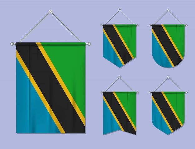 Set di appendere bandiere tanzania con trama tessile. forme di diversità del paese di bandiera nazionale. stendardo modello verticale. Vettore Premium