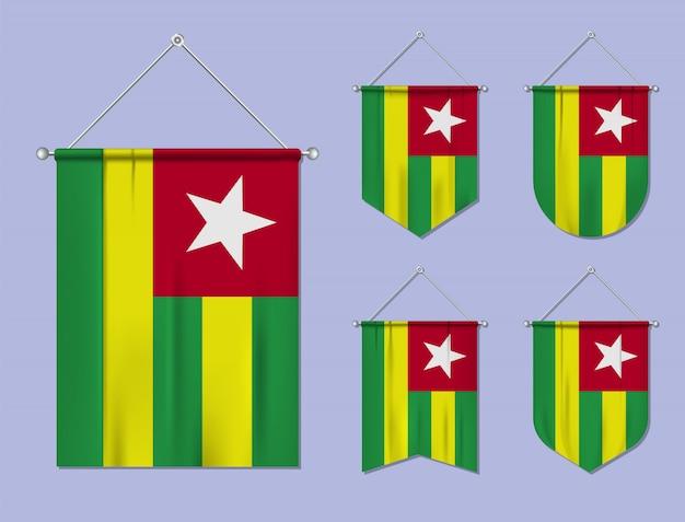 Set di bandiere sospese togo con trama tessile. forme di diversità del paese di bandiera nazionale. stendardo modello verticale. Vettore Premium