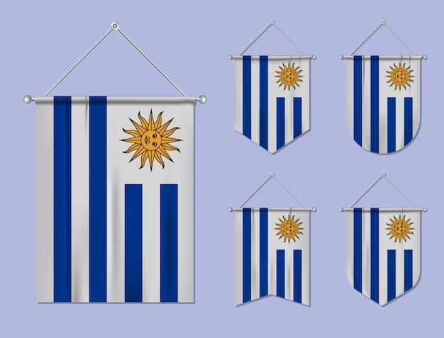 Set di bandiere sospese uruguay con trama tessile. forme di diversità del paese di bandiera nazionale. stendardo modello verticale. Vettore Premium