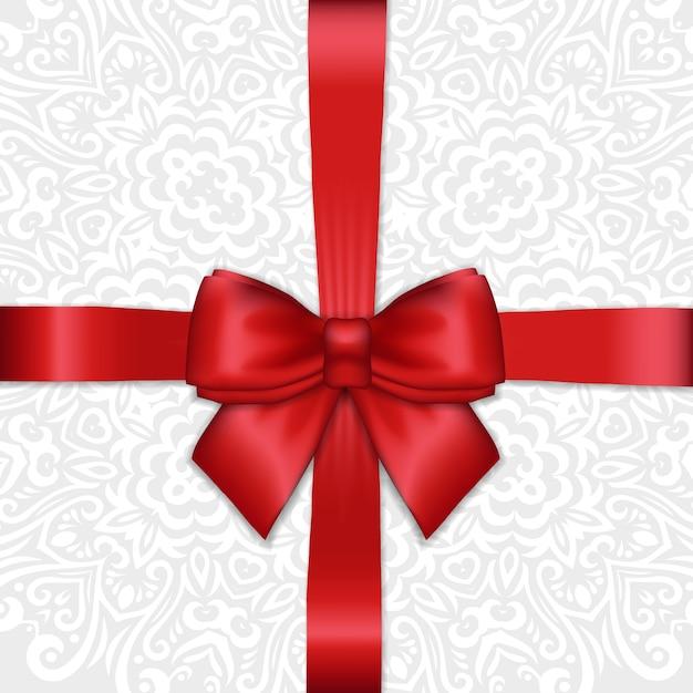 Fiocco di nastro di raso rosso vacanza splendente su sfondo ornamentale di pizzo bianco. Vettore Premium