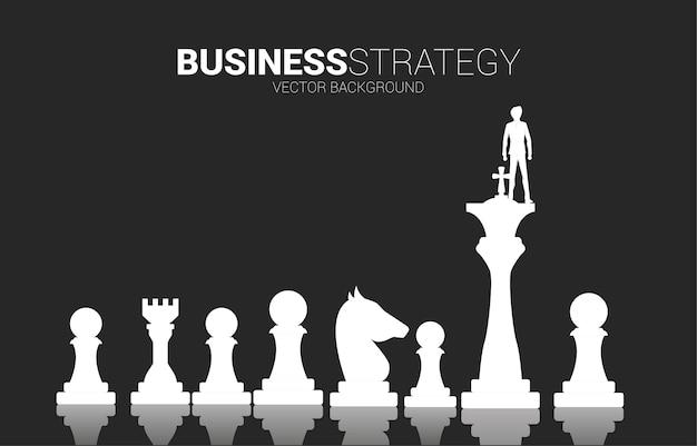 Siluetta dell'uomo d'affari sul re del pezzo degli scacchi. concetto di business di pianificazione strategica e successo Vettore Premium