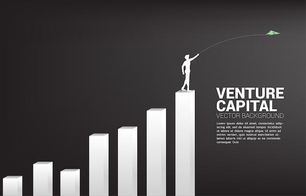 La siluetta dell'uomo d'affari getta l'aeroplano di carta di origami della banconota dei soldi dal grafico della pila. concetto di business di avviare business e imprenditore Vettore Premium