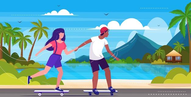Coppia di pattinatori eseguendo acrobazie sul concetto di skateboard sul lungomare Vettore Premium