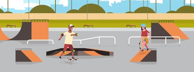 Pattinatori eseguendo trucchi nel parco skate board pubblico con varie rampe per lo skateboarding mix gara adolescenti coppia divertirsi cavalcando skateboard paesaggio Vettore Premium