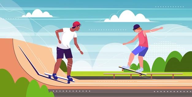 Pattinatori che eseguono acrobazie nel parco pubblico di skateboard con varie rampe per lo skateboard Vettore Premium