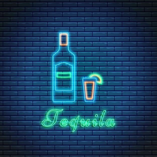 Bottiglia e vetro di tequila con iscrizione nello stile al neon sul fondo del mattone. cocktail bar simbolo, logo, cartello. Vettore Premium