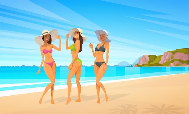 Tre donne in bikini sulla spiaggia Vettore Premium