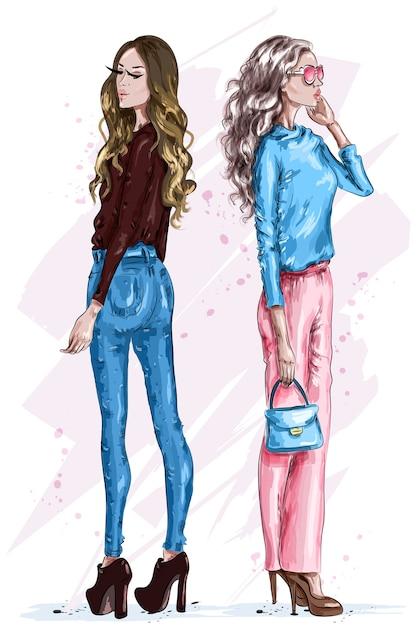 Due belle donne alla moda in vestiti di moda Vettore Premium