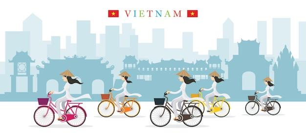 Donne vietnamite con punti di riferimento di biciclette giro cappello conico Vettore Premium