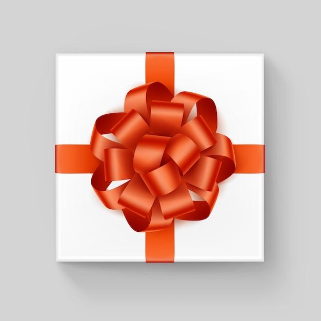 Scatola regalo quadrata bianca con fiocco in nastro arancione lucido vicino vista dall'alto isolato su sfondo Vettore Premium