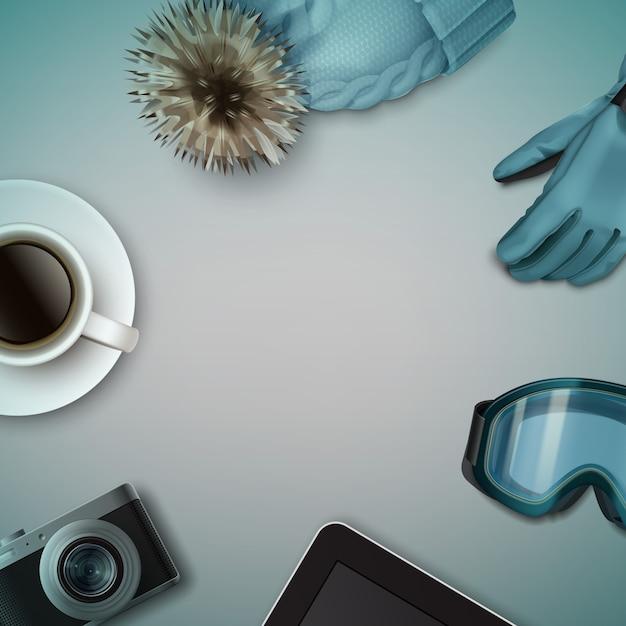 Natura morta invernale: berretto lavorato a maglia blu con pom-pom, guanto, occhiali da sci, tazza di caffè, macchina fotografica, tablet e vista dall'alto Vettore Premium