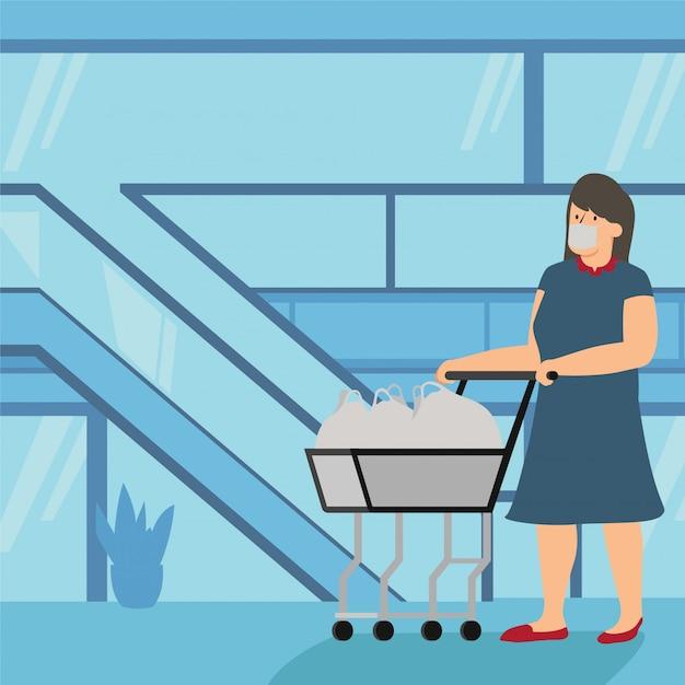 Una donna che porta il suo carrello in carrello al centro commerciale Vettore Premium