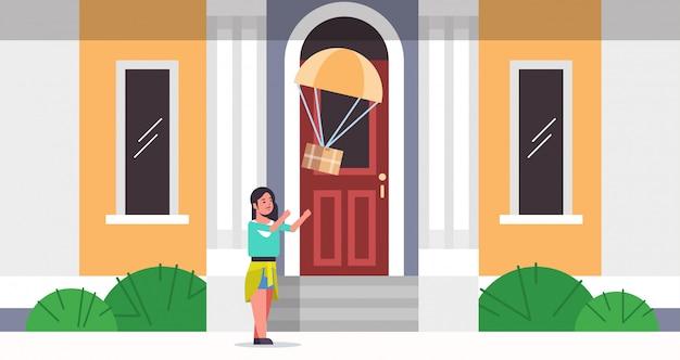 Donna che cattura la scatola pacchi cadere con il paracadute dal cielo trasporto pacchetto di spedizione posta aerea espresso concetto di consegna moderna casa edificio esterno a figura intera piatta orizzontale Vettore Premium