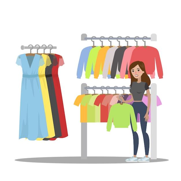 Donna che sceglie i vestiti nel negozio di abbigliamento. alla ricerca di una felpa con cappuccio alla moda. illustrazione Vettore Premium
