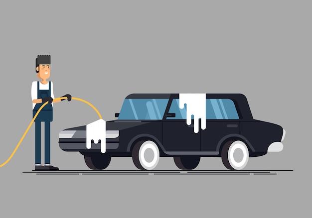 Lavoratore che lava un'auto all'autolavaggio. Vettore Premium