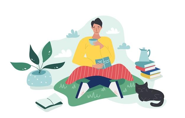 Il giovane ragazzo che si siede sull'erba con un plaid e legge un libro mentre beve una tazza di tè o caffè nel giorno nuvoloso. un gatto nero dorme qui vicino. illustrazione piatta di cartone colorato. Vettore Premium
