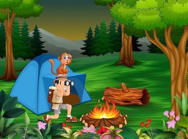 Zookeeper e la sua scimmia si accampano nella foresta oscura Vettore Premium