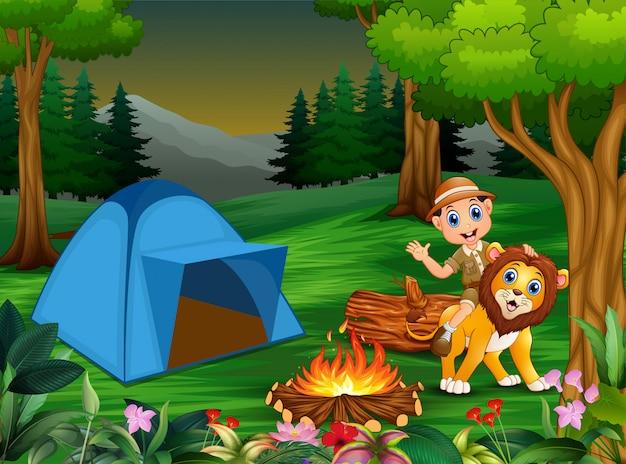 Zookeeper ragazzo e un leone accanto alla tenda e falò Vettore Premium