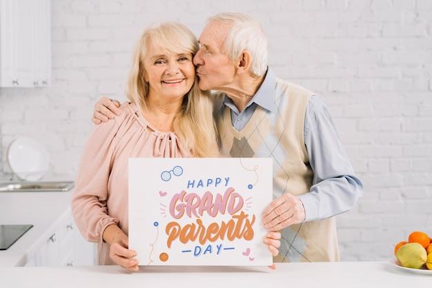 Abuelos sujetando maqueta de cartel PSD gratuito