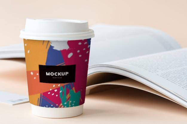 Afhaalmaaltijden koffiekopje mockup op een tafel met een open boek Gratis Psd