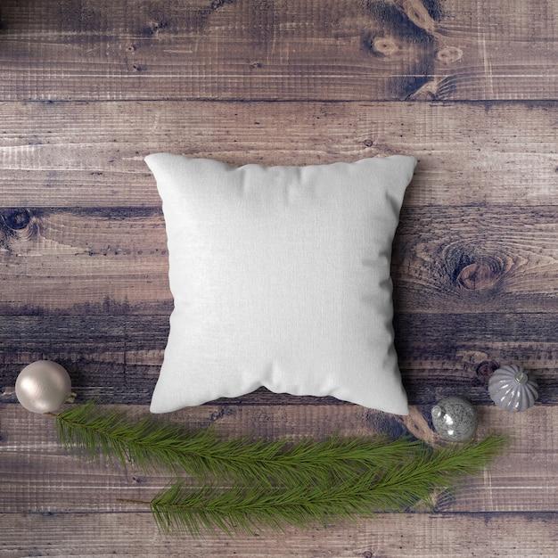 Almohada sobre una mesa de madera rodeada de adornos, pinos y abetos PSD gratuito