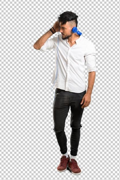 Arabische jongeman met wit overhemd luisteren naar muziek met een koptelefoon Premium Psd
