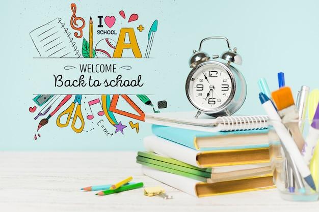 Arreglo con libros escolares y reloj PSD gratuito