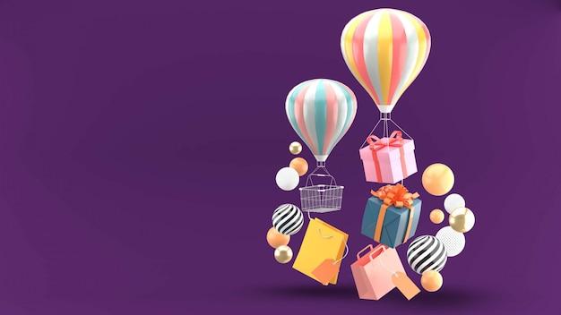 Ballon, geschenkdoos en boodschappentas omgeven door kleurrijke ballen op paars Premium Psd
