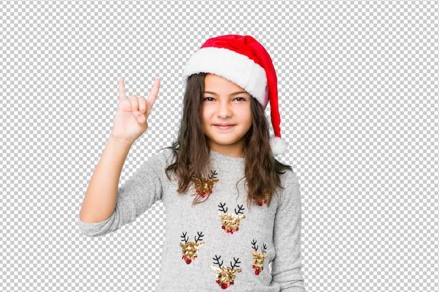 Bambina che celebra il giorno di natale che mostra un gesto dei corni come concetto di rivoluzione. Psd Premium