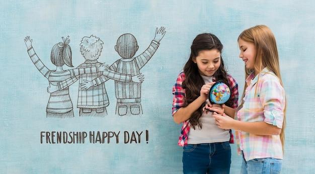 Bambini in possesso di un globo terrestre con parete mock-up Psd Gratuite