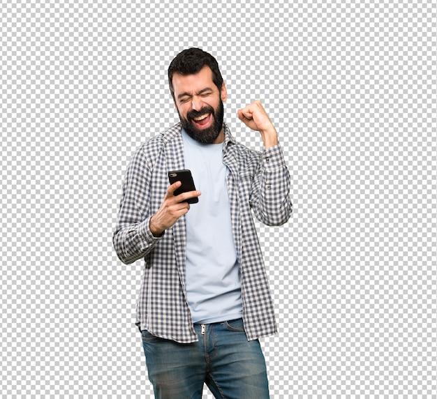 Bell'uomo con la barba con il telefono in posizione di vittoria Psd Premium
