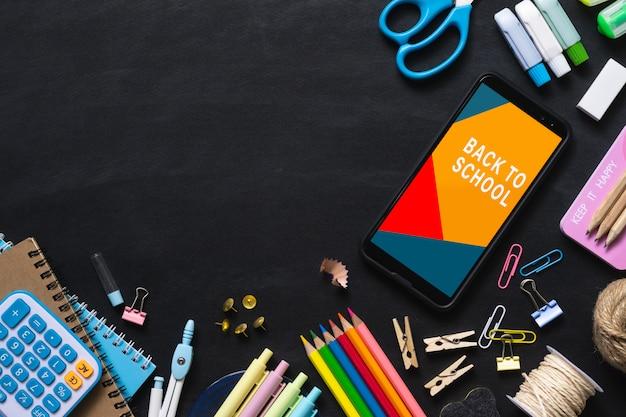 Bespotten mobiele telefoon voor terug naar school achtergrond concept. Premium Psd