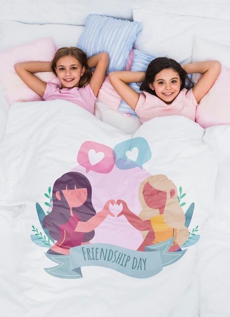 Beste vrienden ontspannen in bed met schattige deken mock-up Gratis Psd