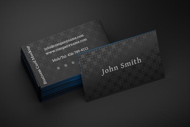 Bewerkbare mock up van een stapel zwarte visitekaartjes met een staande kaart op zwart Premium Psd