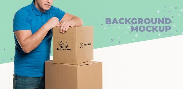 Bezorger die zichzelf ondersteunt op een stel dozen met een achtergrondmodel Gratis Psd