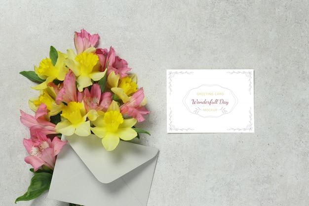 Biglietto d'invito con fiori gialli e rosa, busta grigia Psd Premium